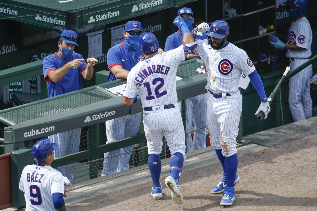 Chicago Cubs' Kyle Schwarber, center celebrates with Jason Heyward, right, after hitting a two-run home run against the Chicago White Sox during the s...
