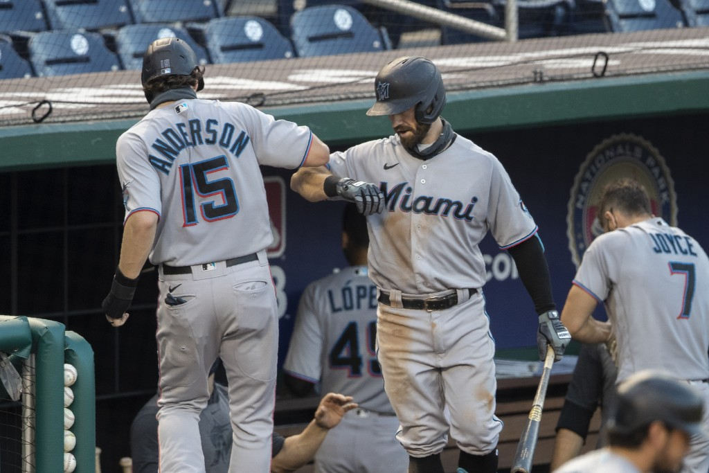 Miami Marlins' Brian Anderson (15) is congratulated by teammate Jon Berti (5) after scoring on Jonathan Villar's single during the fourth inning of a ...