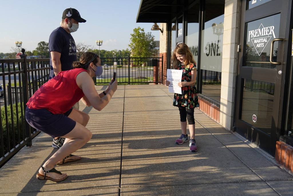 Paul Quisenberry watches as his wife, Jennifer Quisenberry, front left, takes a picture of their daughter Audra, 6, as the first grader prepares to en...