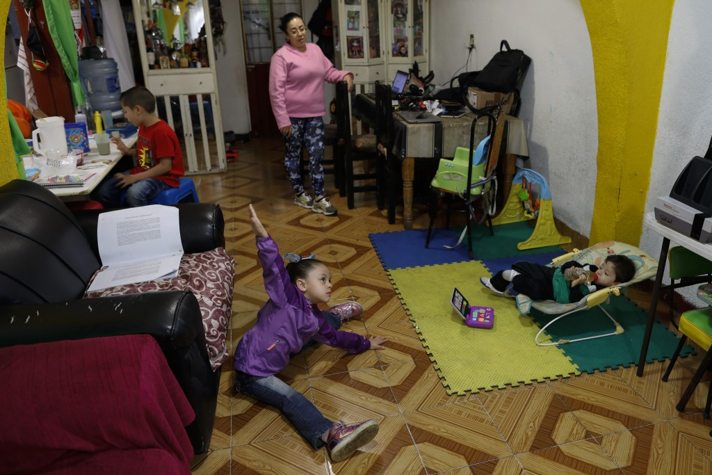 Liz, 5, follows along with the physical education segment of a televised pre-kindergarten class, as her mother Denisse and two siblings look on, insid...