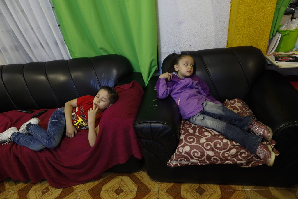 Santi, 6, and his sister Liz, 5, struggle to focus on a televised kindergarten lesson as students return to classes but not schools in Mexico City, Mo...