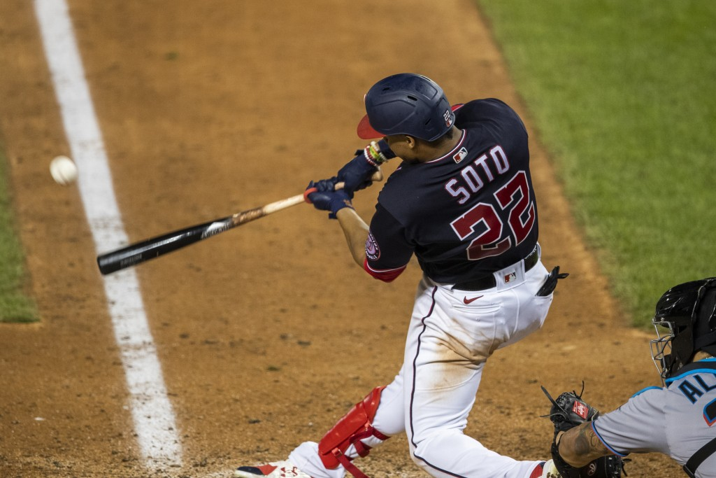 Washington Nationals' Juan Soto (22) hits a one-run double during the seventh inning of a baseball game against the Miami Marlins in Washington, Monda...
