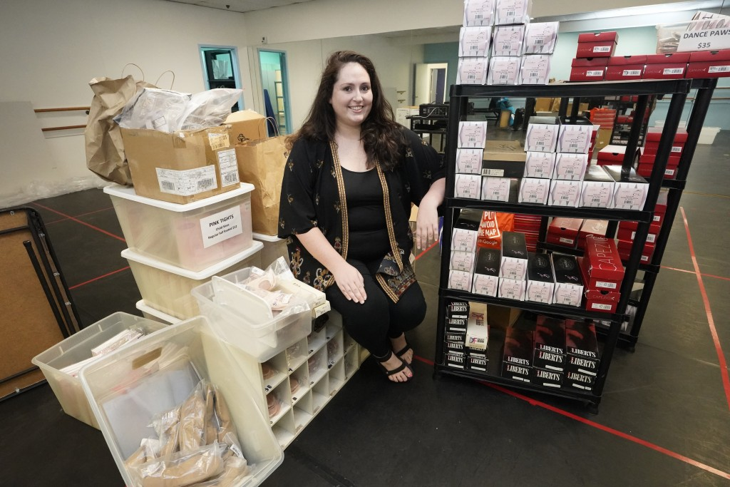 Katie Goughan, owner of Dance Explosion Co. studio, poses for a photo with dance supplies at her studio, Thursday, Aug. 13, 2020, in Hollywood, Fla. H...