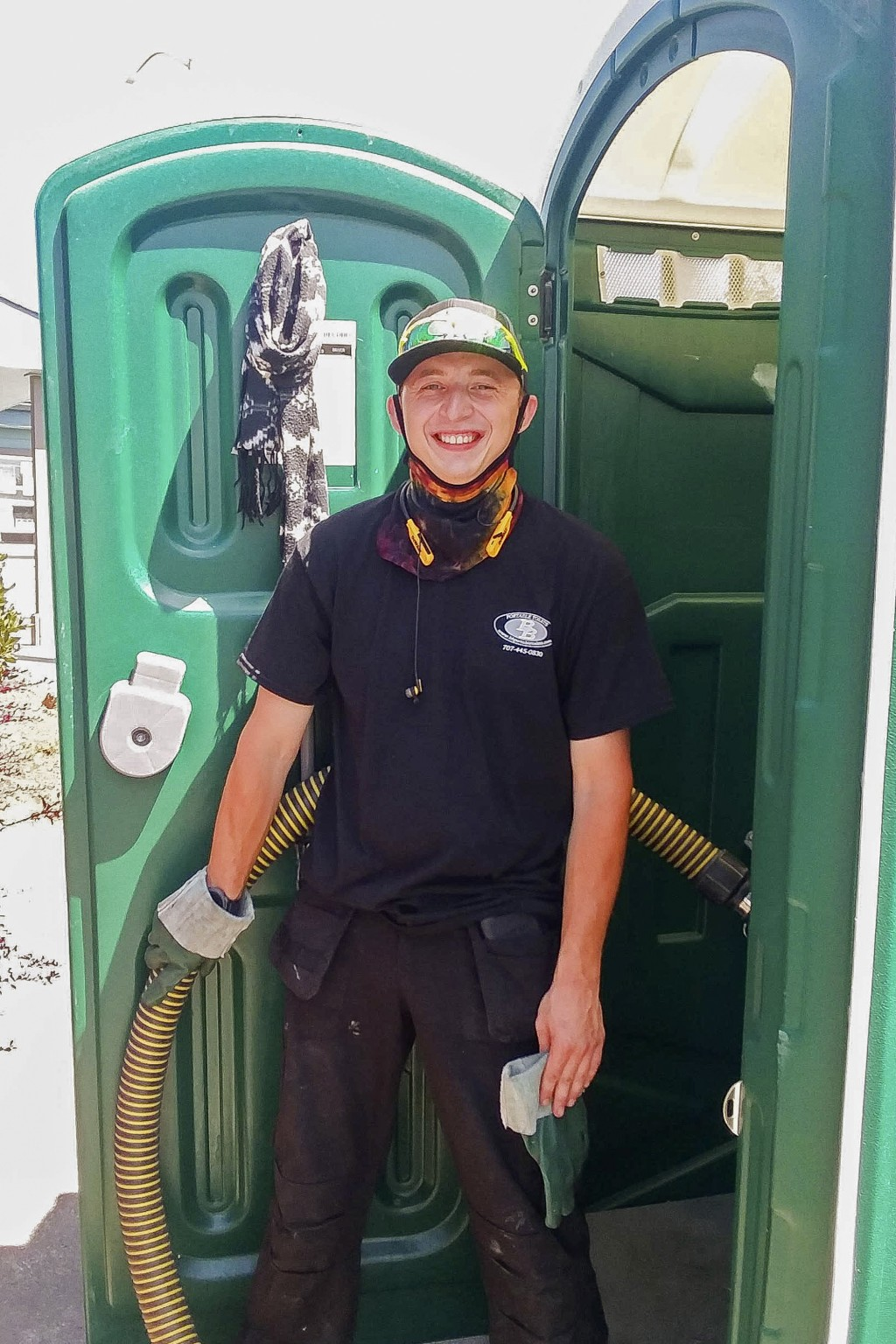 Donnie Settles, 27, stands near a portable toilet on July 14, 2020, which he services for his employer in Arcata, Calif. Settles lived at an emergency...