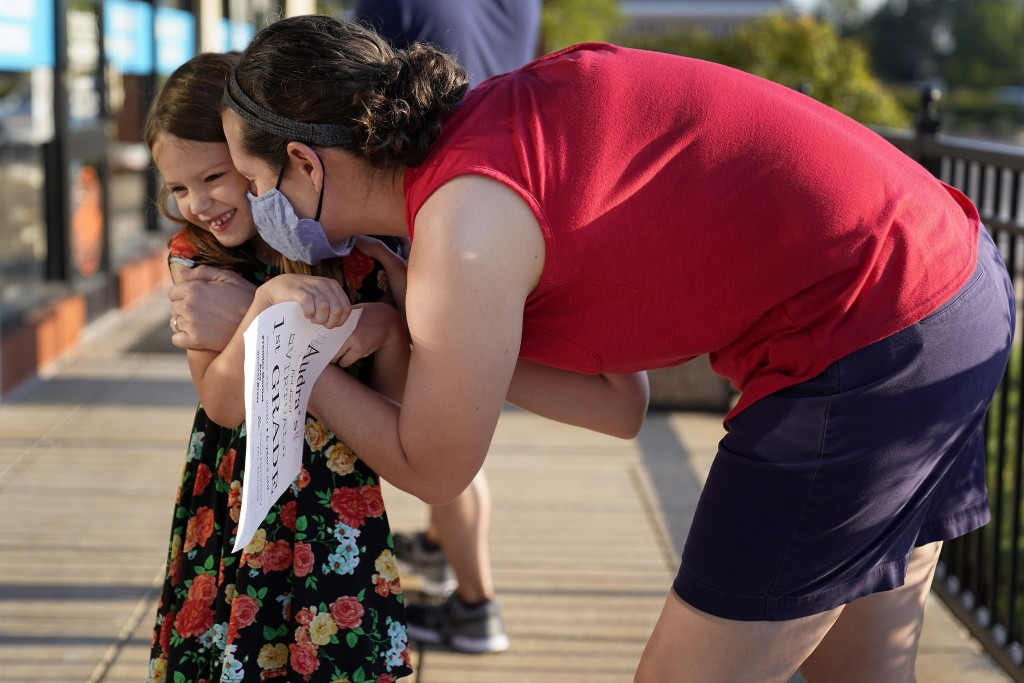 Jennifer Quisenberry hugs her daughter Audra, 6, as she is dropped off at Premier Martial Arts on her first day of school Monday, Aug. 24, 2020, in Wi...