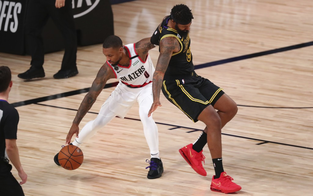 Portland Trail Blazers guard Damian Lillard (0) steals the ball from Los Angeles Lakers forward Markieff Morris, right, in the second half of Game 4 o...