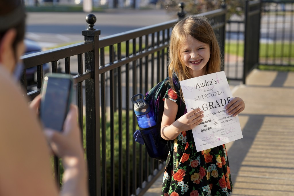 Jennifer Quisenberry takes a picture of her daughter Audra, 6, as she prepares to enter Premier Martial Arts on her first day of school Monday, Aug. 2...