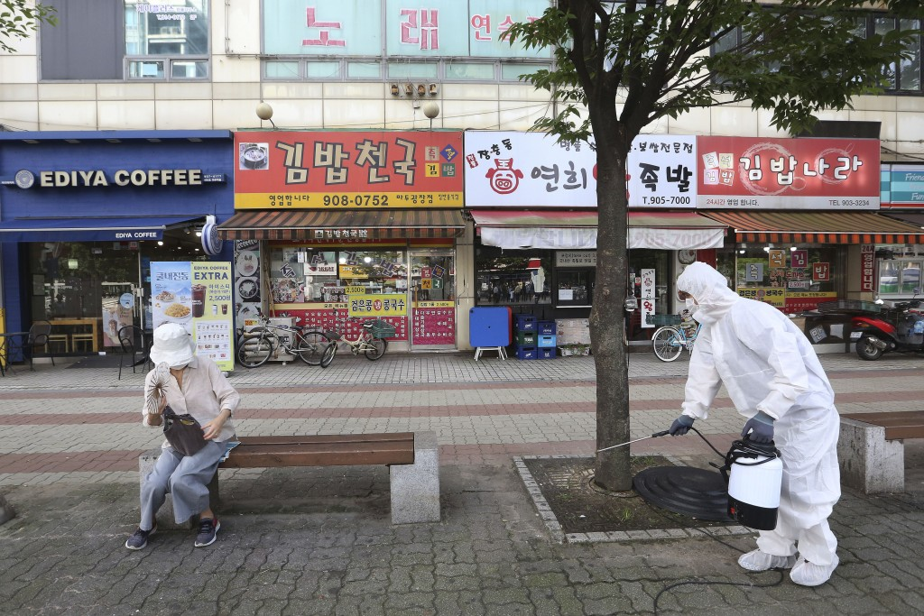 A worker disinfects as a precaution against the coronavirus on a street in Goyang, South Korea, Tuesday, Aug. 25, 2020. South Korea is closing schools...
