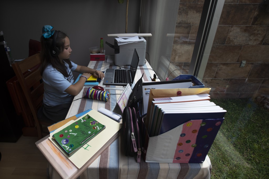 Ixchel Hannia Luna Calonico attends school via the internet from her home amid the new coronavirus pandemic in Mexico City, Monday, Aug. 24, 2020. A s...