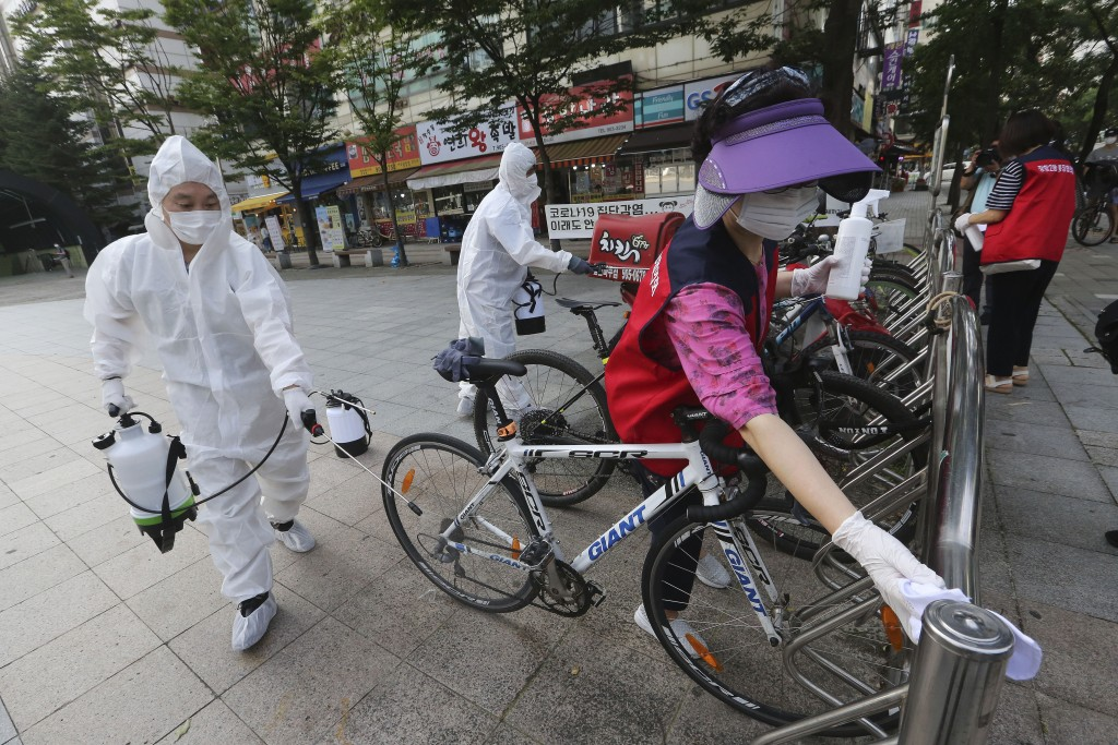 Workers and volunteers disinfect as a precaution against the coronavirus on a street in Goyang, South Korea, Tuesday, Aug. 25, 2020. South Korea is cl...