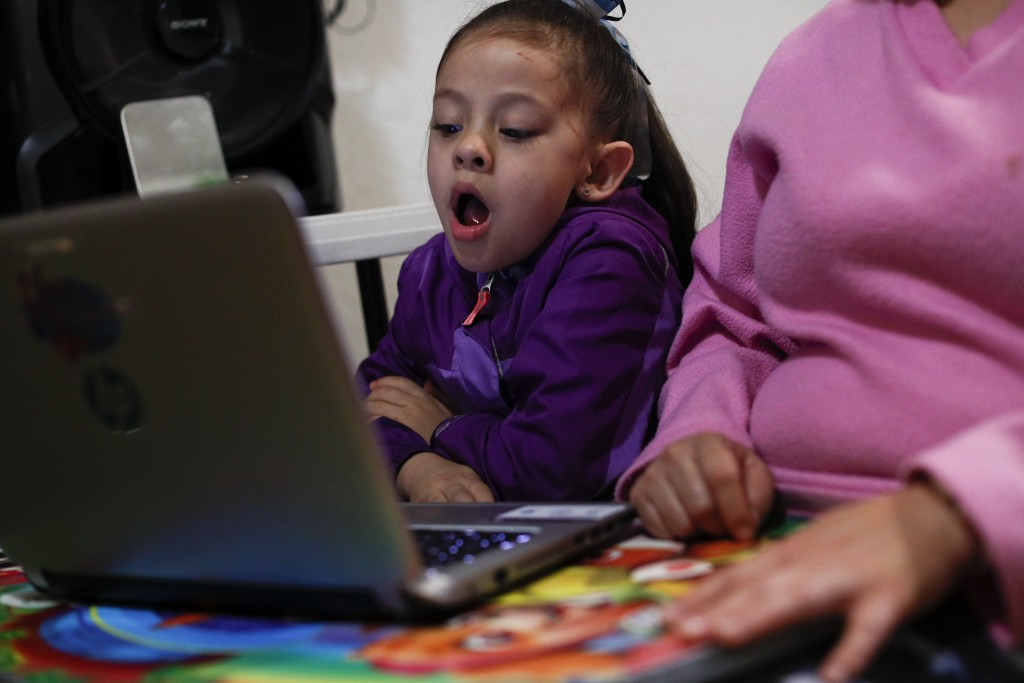Liz, 5, yawns as she follows along with an online pre-kindergarten class, as students return to classes but not schools in Mexico City, Monday, Aug. 2...