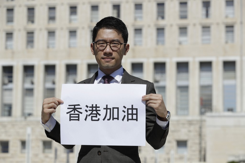 "Hong Kong activist Nathan Law holds a banner reading in Chinese ""Go Hong Kong"" as he takes part in a protest during a meeting of Chinese Foreign Minis..."