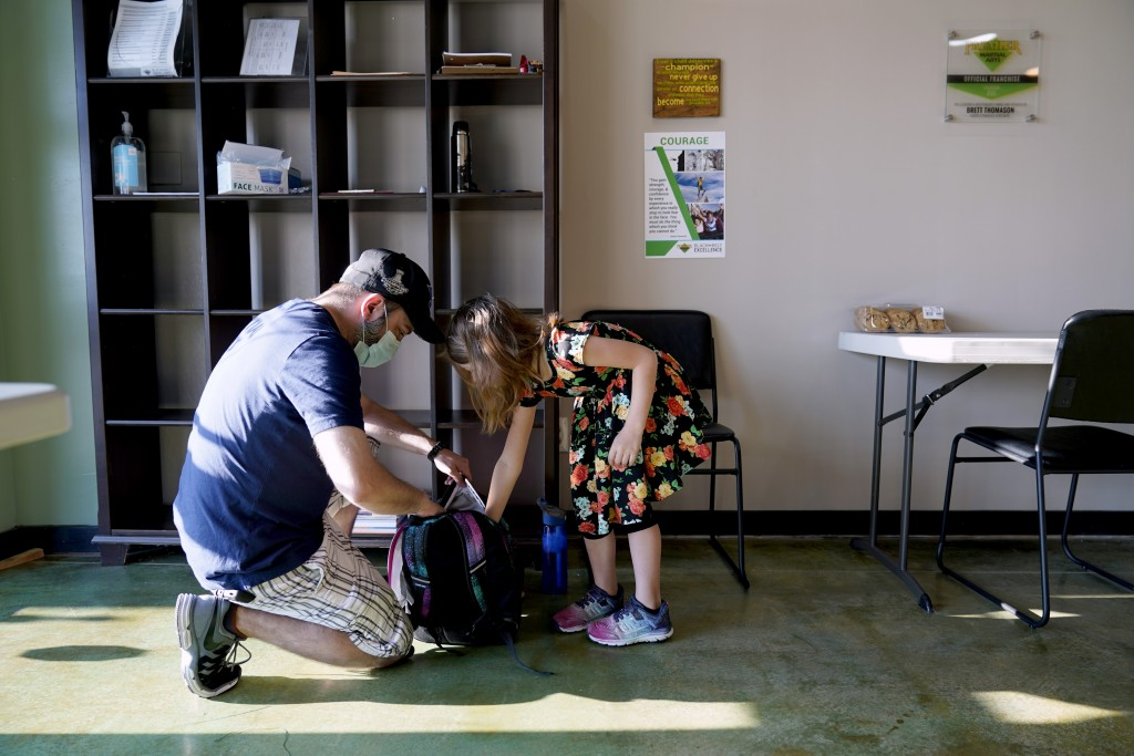 Paul Quisenberry helps his daughter Audra, 6, get organized as he drops her off at Premier Martial Arts on her first day of school Monday, Aug. 24, 20...