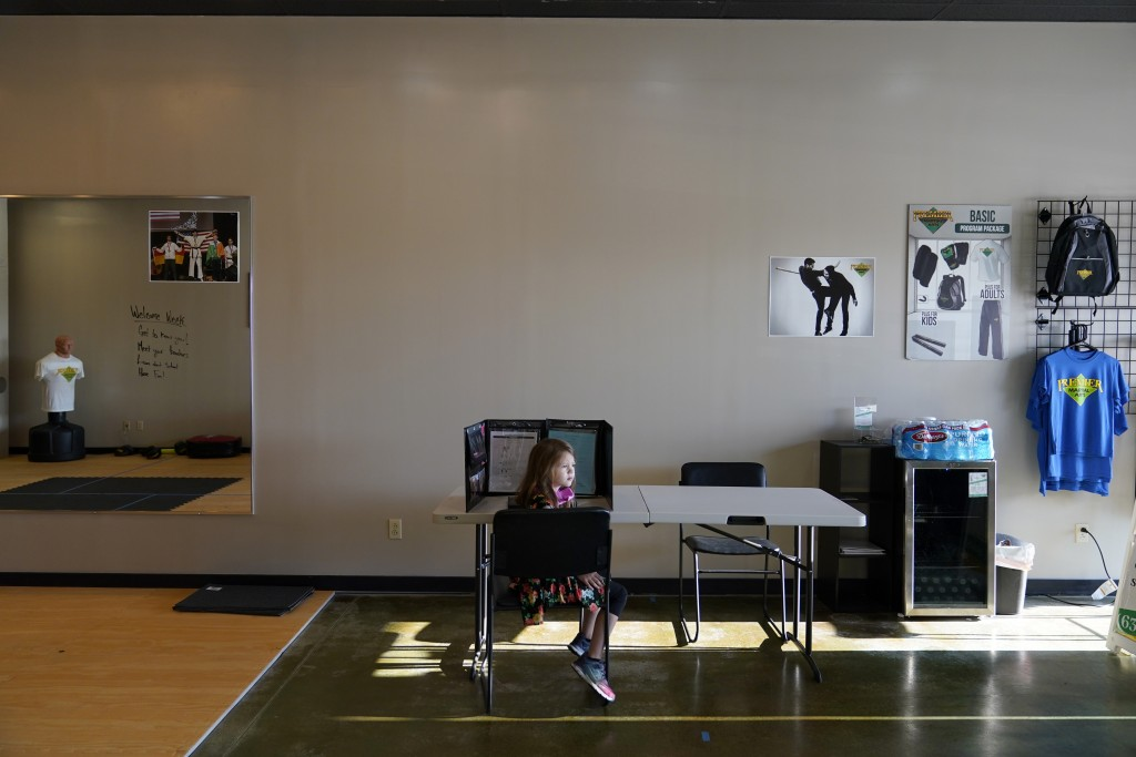 Audra Quisenberry, 6, waits for other children to arrive as she sits at her desk inside Premier Martial Arts on her first day of school Monday, Aug. 2...