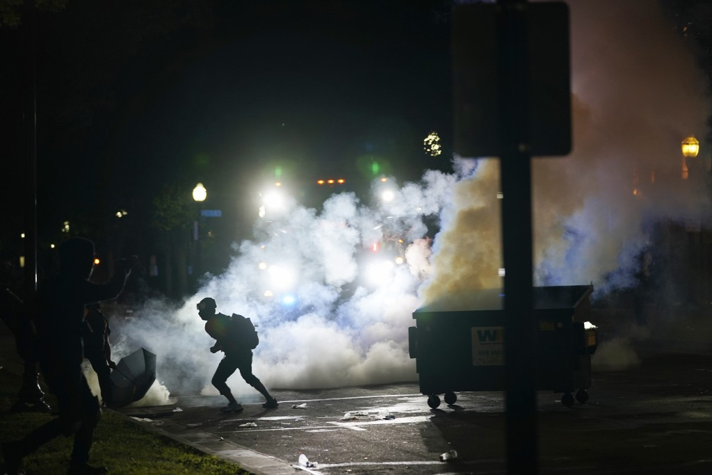 A protester moves away from a smoke canister Tuesday, Aug. 25, 2020 in Kenosha, Wis. Anger over the Sunday shooting of Jacob Blake, a Black man, by po...