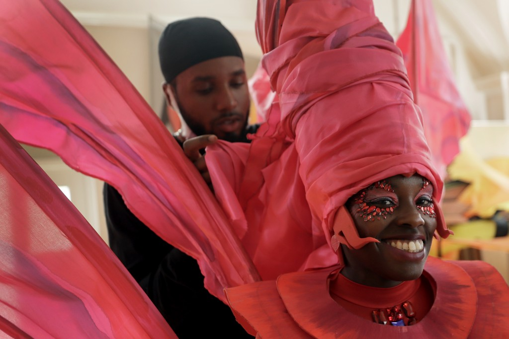Jez Smith helps Ebony Beckford to get her costume ready for a prepping event ahead of this years Notting Hill Carnival which will be held virtually, i...