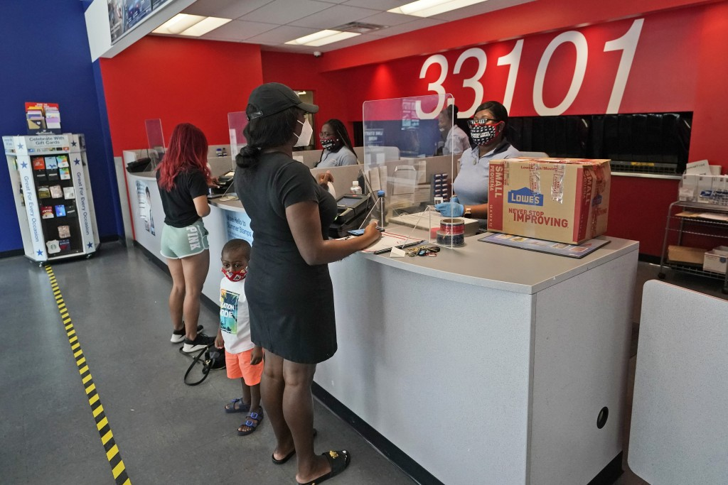 Postal workers attend customers at the Flagler Station post office, Tuesday, Aug. 25, 2020, in Miami. The pandemic has pushed the Postal Service into ...