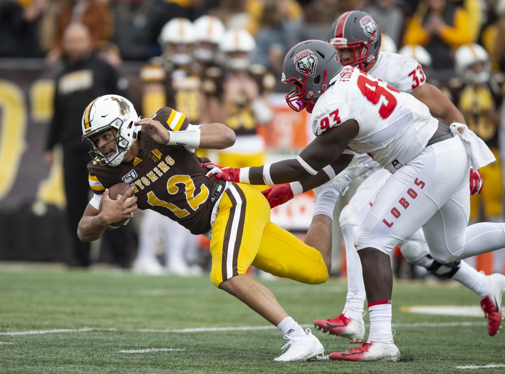 FILE - In this Oct. 19, 2019, file photo, Wyoming quarterback Sean Chambers (12) runs against New Mexico's Nahje Flowers during an NCAA college footba...
