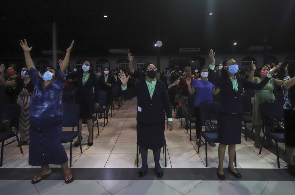Women wearing masks to curb the spread of the new coronavirus pray during the afternoon service at the Bethel evangelical church in Managua, Nicaragua...