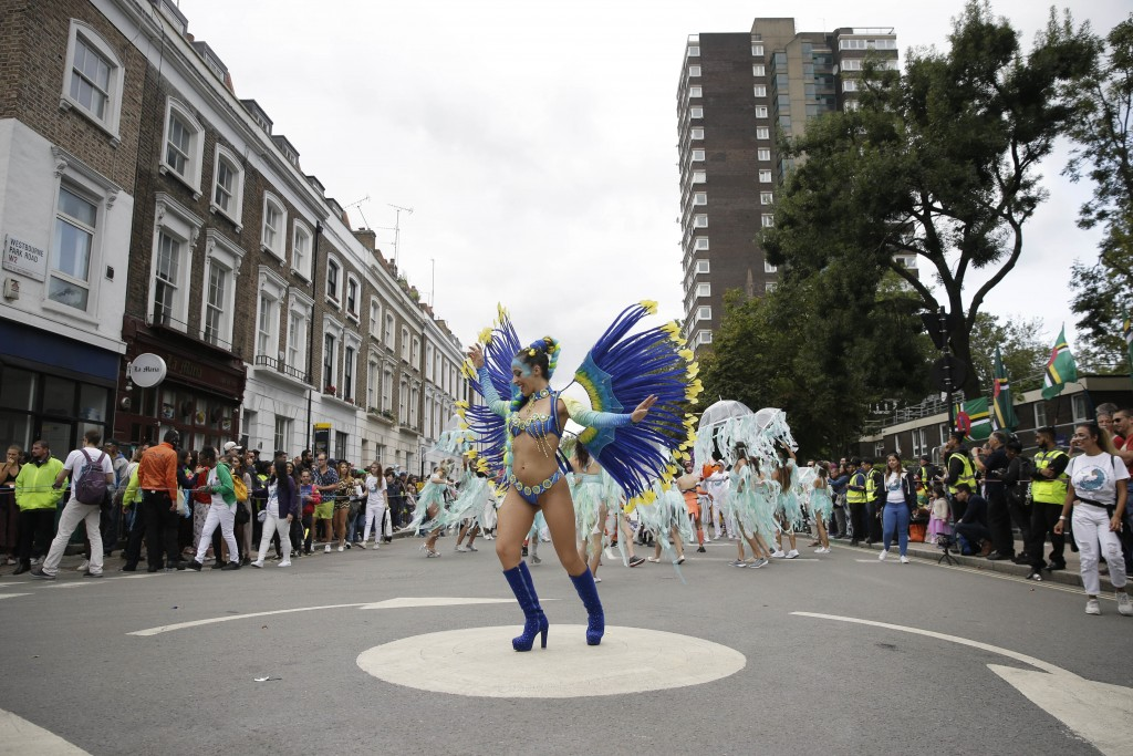 FILE - In this Monday, Aug. 27, 2018 file photo, costumed revellers perform in the parade during the Notting Hill Carnival in London.  London's Nottin...