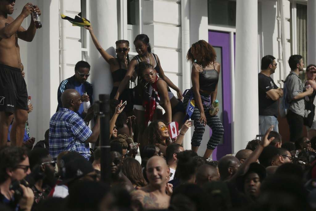 FILE - In this Monday, Aug. 28, 2017 file photo, revellers dace on the wall of a house on Ladbroke Grove during the Notting Hill Carnival in London. L...