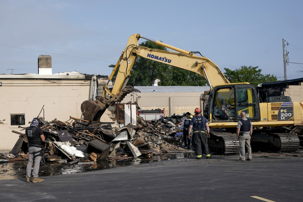 ATF agents look over the damage at an office supply company that was burned during a protest Tuesday, Aug. 25, 2020, in Kenosha, Wis. (AP Photo/Morry ...