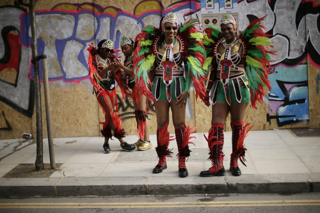 FILE - In this Monday, Aug. 27, 2018 file photo, costumed revellers pose ahead of the parade during the Notting Hill Carnival in London. London's Nott...