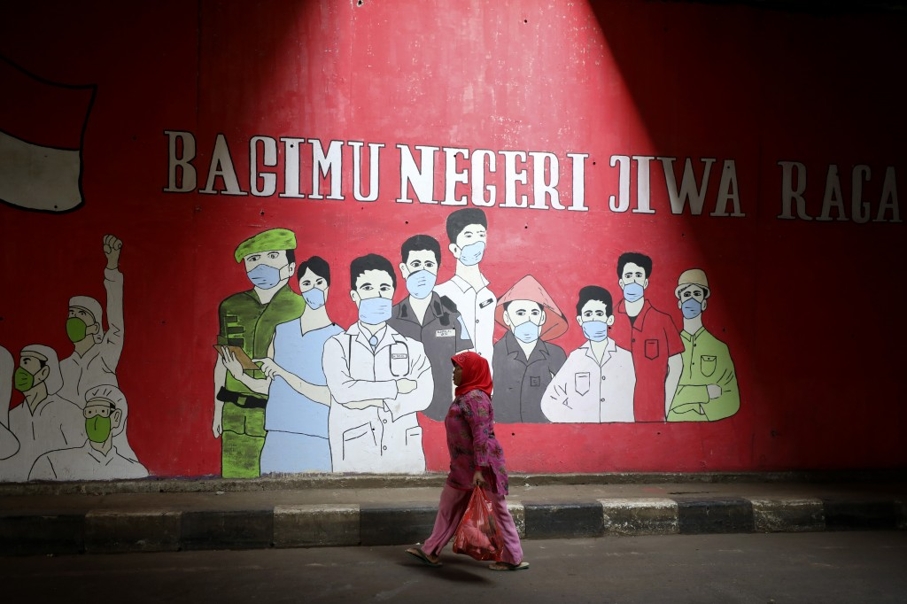 A woman walks past a coronavirus-themed mural in Jakarta, Indonesia.