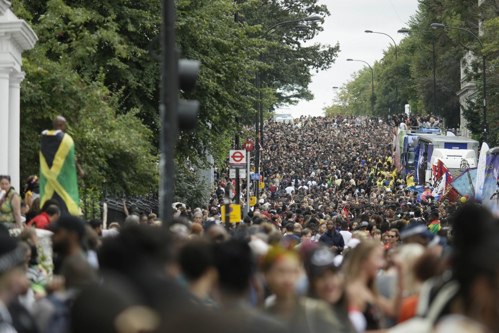 FILE - In this Monday, Aug. 27, 2018 file photo, crowds on Ladbroke Grove take part in the parade during the Notting Hill Carnival in London. London's...