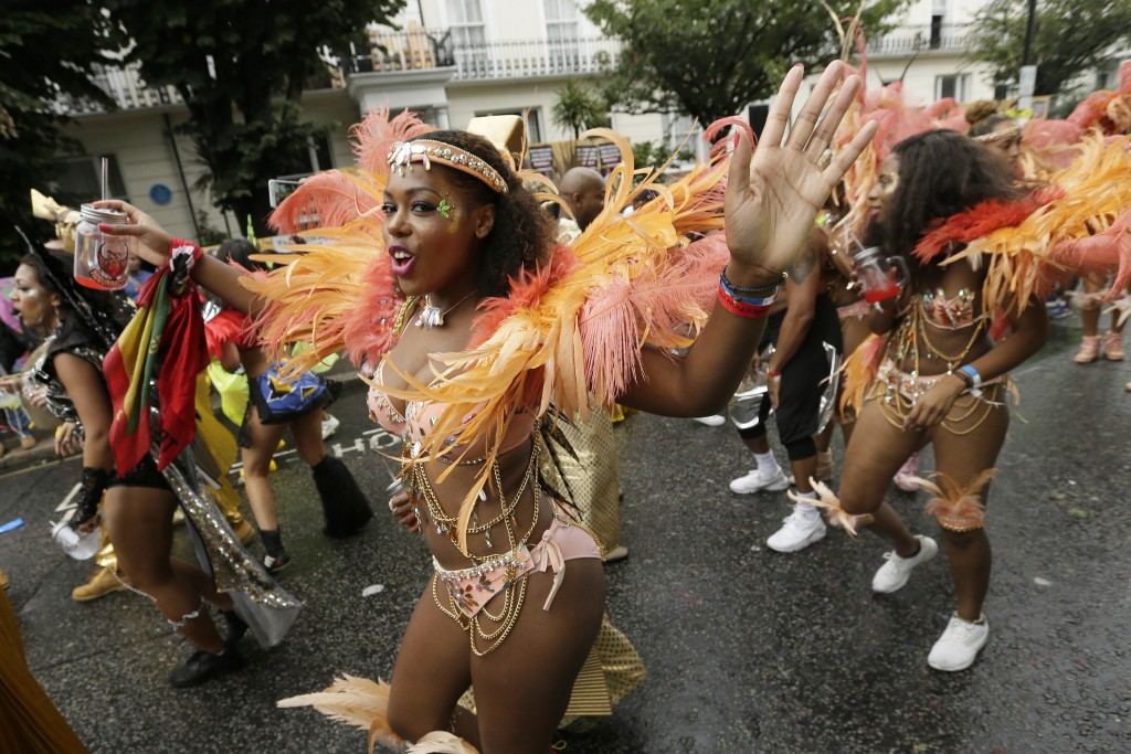 FILE - In this Monday, Aug. 31, 2015 file photo, a costumed reveller performs in the Notting Hill Carnival in London. London's Notting Hill Carnival t...