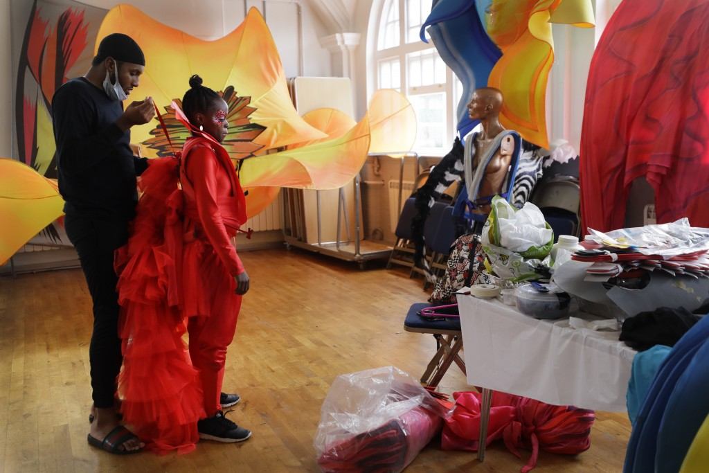 Jez Smith helps Ebony Beckford to get her costume ready for a prepping event ahead of this year's Notting Hill Carnival which will be held virtually, ...