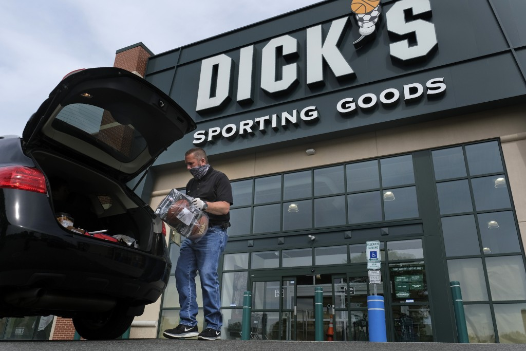 FILE - In this May 18, 2020 file photo, Gus Promollo delivers an order into a customer's trunk at Dick's Sporting Goods in Paramus, N.J.  At home work...