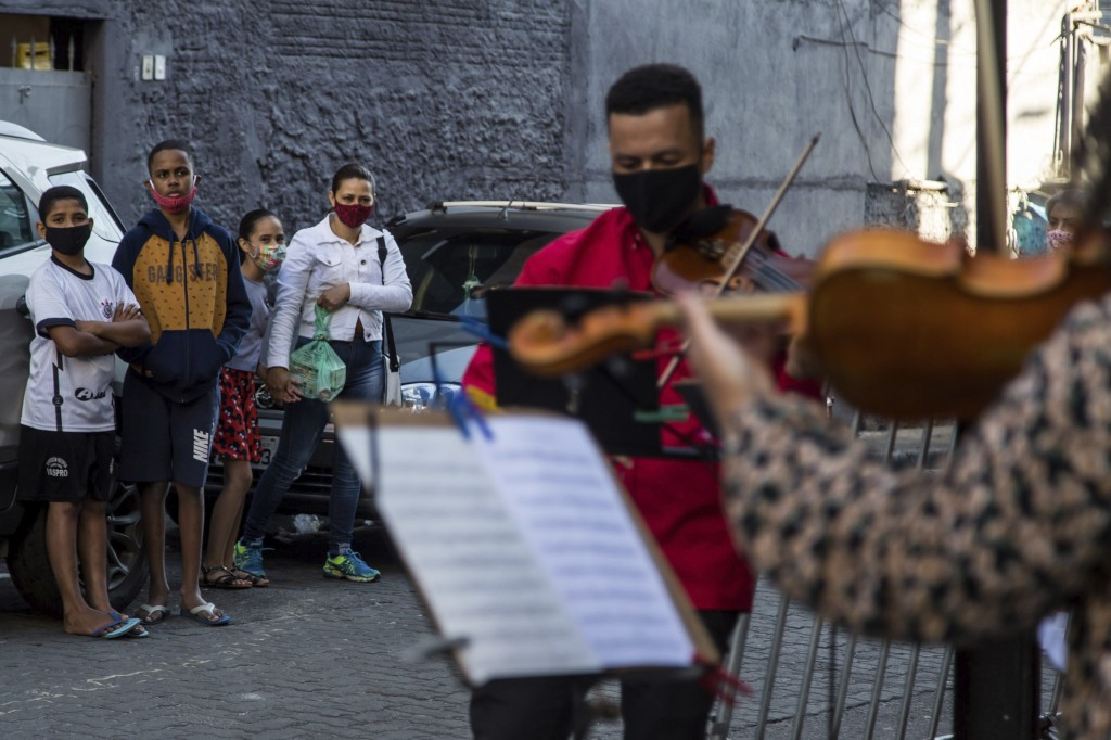 Locals watch students from the Baccarelli Institute play music on a street in the Heliopolis neighborhood of Sao Paulo, Brazil, Tuesday, Aug. 25, 2020...