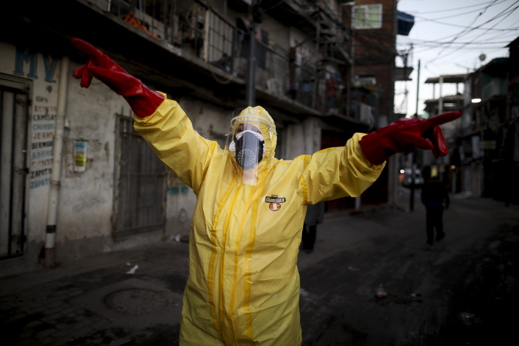 FILE - In this Monday, May 18, 2020 file photo, Jimena Aballe directs her neighbors as they disinfect their own streets in the Villa 31 neighborhood t...
