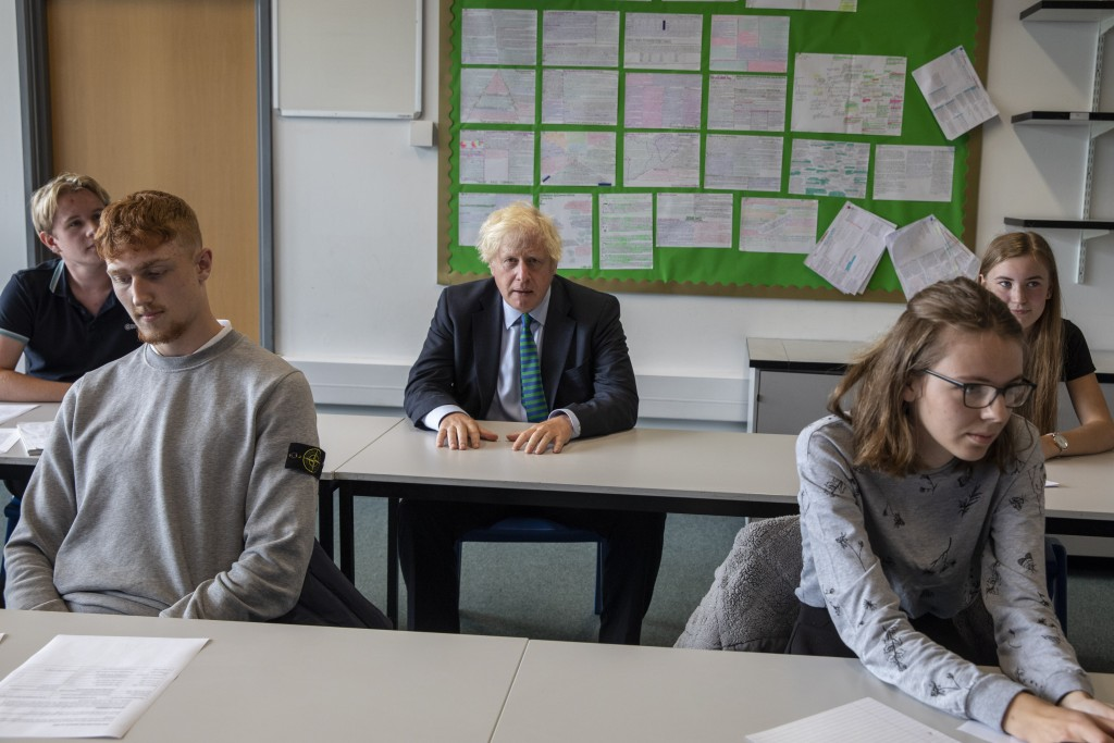 Britain's Prime Minister Boris Johnson sits in a Year 11 class, during a visit to Castle Rock school on the pupils' first day back, in Coalville, East...