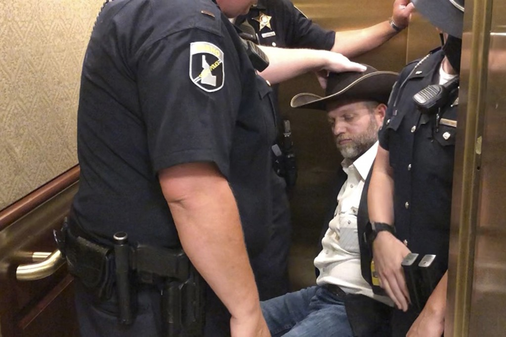 This image taken from video shows anti-government activist Ammon Bundy, rear, being wheeled into an elevator in a chair following his arrest at the Id...