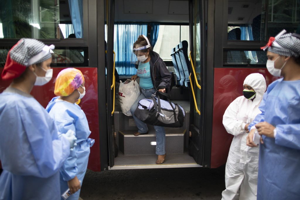 A woman who tested positive for COVID-19 arrives on a government bus to a former students residence being used to quarantine asymptomatic patients inf...