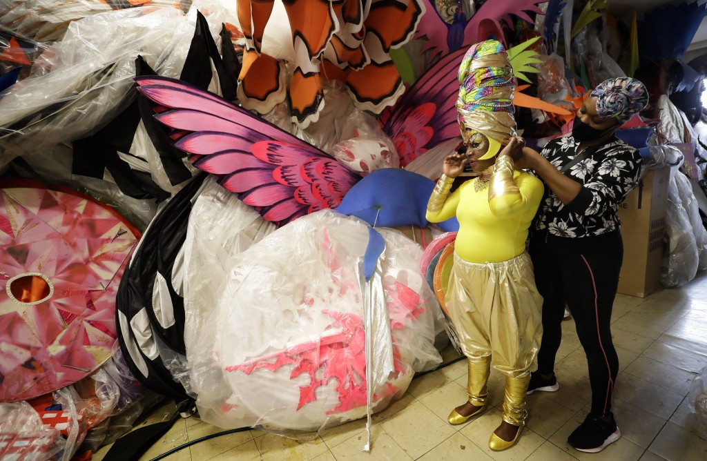 Anucska Case assists Carolyn Roberts-Griffith with her costume for a prepping event ahead of this year's Notting Hill Carnival which will be held virt...