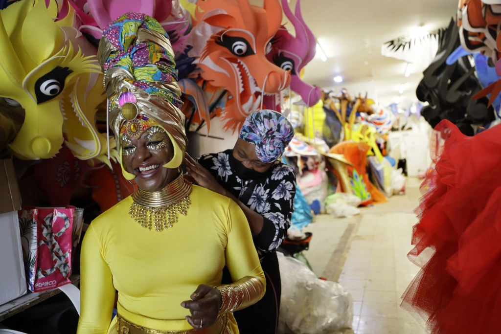 Anucska Case assists Carolyn Roberts-Griffith, left, with her costume for a prepping event ahead of this years Notting Hill Carnival which will be hel...