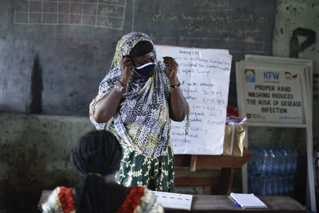 A trainee demonstrates how to safely remove a face mask for protection against the coronavirus, at a training session for community health workers con...
