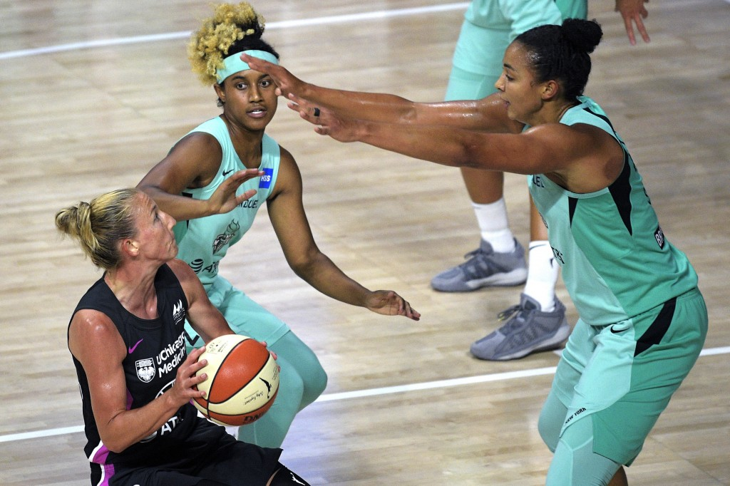 Chicago Sky guard Courtney Vandersloot, left, drives to the basket in front of New York Liberty center Kiah Stokes, right, and guard Paris Kea during ...