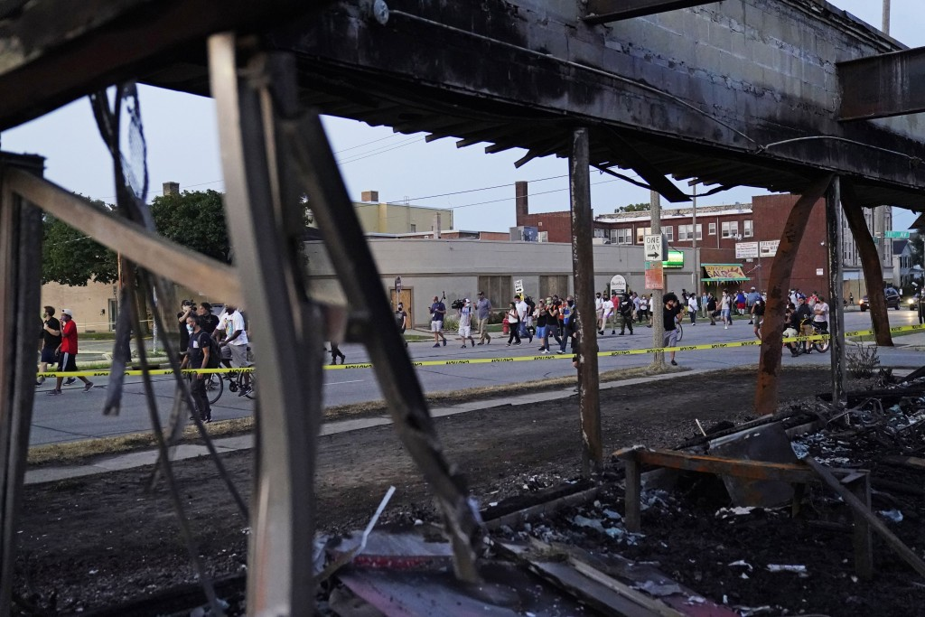 Protesters march past a burned out building damaged in protests against the Sunday police shooting of Jacob Blake in Kenosha, Wis., Wednesday, Aug. 26...