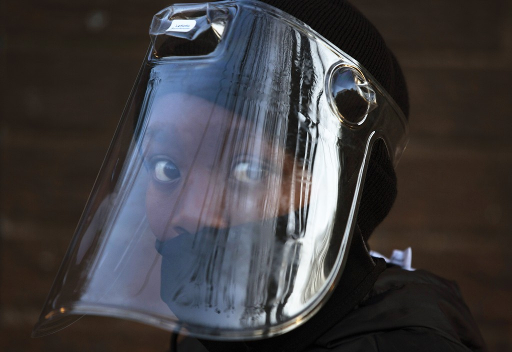 FILE — In this Aug. 24, 2020 file photo, a student, wearing a face mask and shield, returns to the Melpark Primary School in Johannesburg after severa...