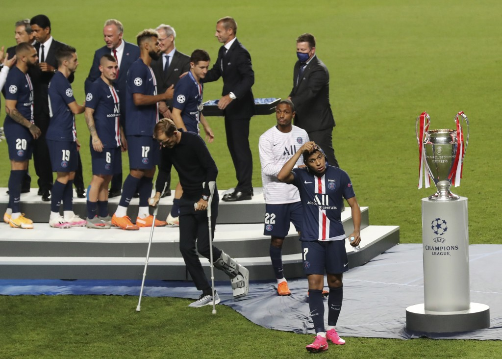 FILE - In this Sunday, Aug. 23, 2020 file photo, PSG's Kylian Mbappe, right, walks past the trophy for winners of the Champions League final soccer ma...