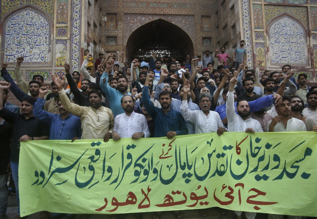 """Supporters of the religious group Jamaat-e-Islami hold a banner reading """"definitely punish those who violate the sanctity of Wazir Khan Mosque"""" at a d..."""