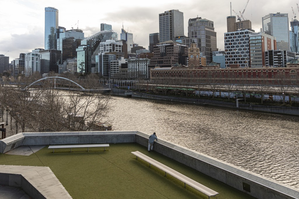 A lone man looks out towards the Yarra River and the empty Central business district during lockdown in Melbourne, Australia, Wednesday, Aug. 5, 2020....