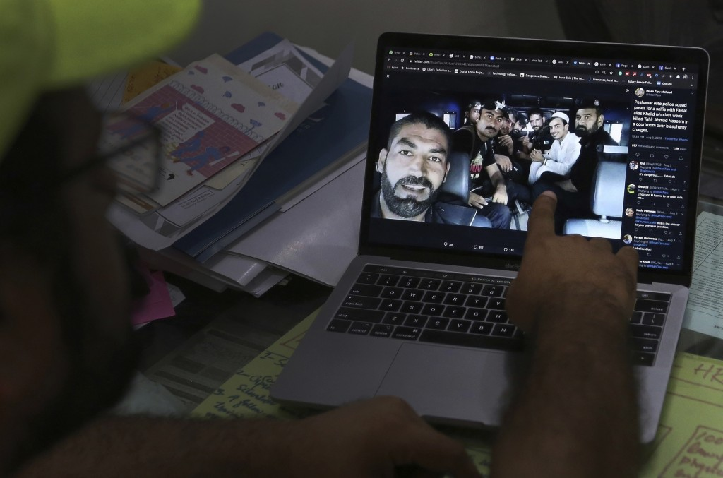 A member of a social media rights group shows a selfie photo of elite police officers taken with Khalid Khan, in white, a smiling gunman who shot and ...
