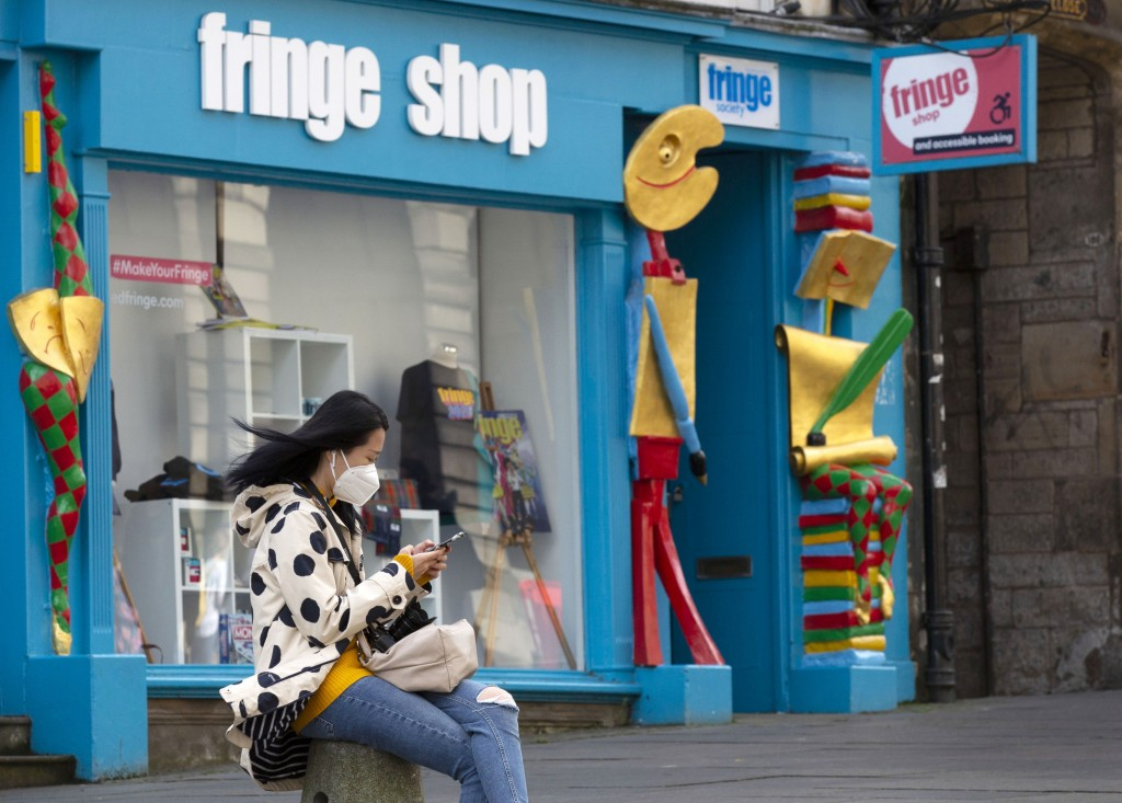 A woman scans her smartphone outside the Fringe Shop on the Royal Mile in Edinburgh, Scotland Friday Aug. 21, 2020.  One of the biggest casualties of ...