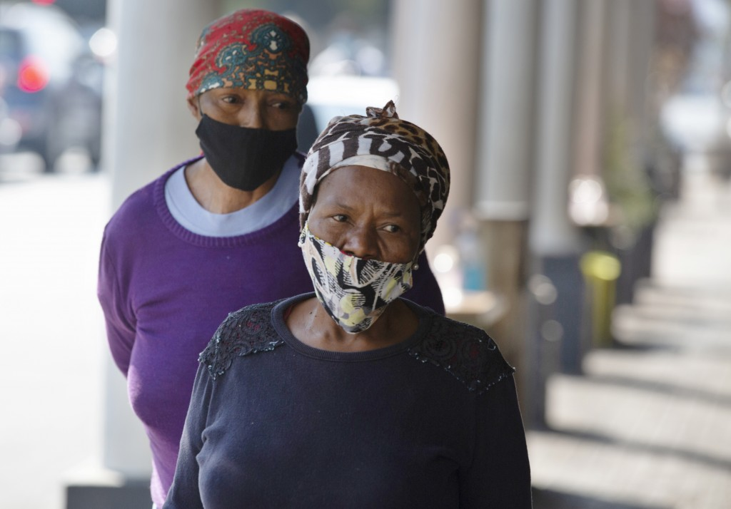 Women wearing face masks walk on a suburban sidewalk in Johannesburg, South Africa on Wednesday, July 22, 2020. Ordinarily, South Africa sees widespre...