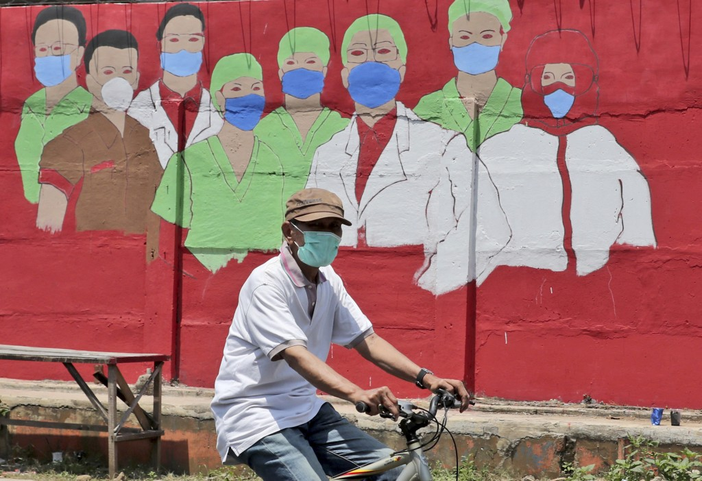 A cyclist rides past a coronavirus-themed mural in Jakarta, Indonesia, Thursday, Aug. 27, 2020.